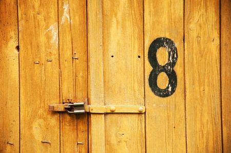 Old wooden garage door with number eight written on it  photo