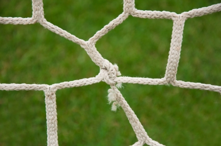 Close up detail of a soccer net against green grass photo