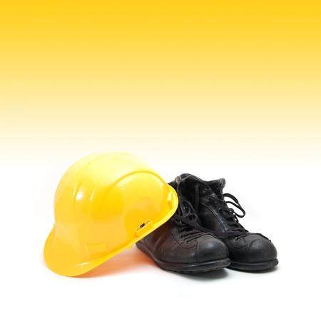 calzado de seguridad: Sombrero amarillo duro y viejas botas de cuero, equipo de protección en la industria de la construcción