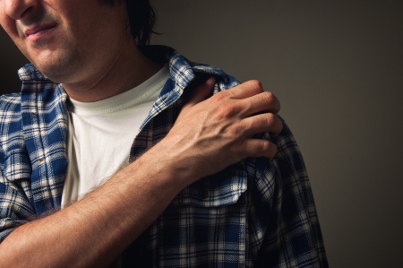 hand on shoulder: Young adult man suffering from severe shoulder pain  Stock Photo