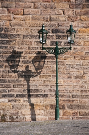 Wrought-iron lantern with its shadow on the yellow wall, Prague, Czech Republic photo