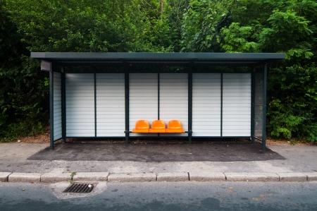 parada de autobus: Estación de autobuses de color naranja con asientos de plástico en el parque Foto de archivo