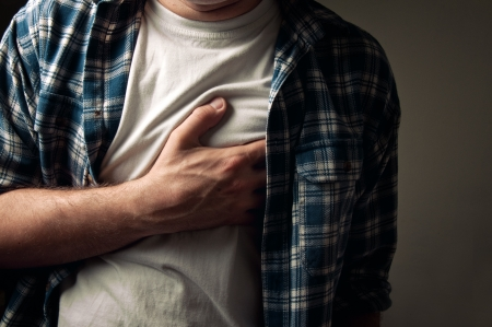 heartache: Young adult man suffering from severe heartache.