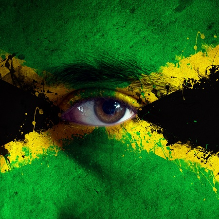 rasta colors: jamaican flag painted on face of a national team supporter, close up of a male eye