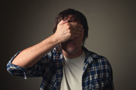 Young adult casual man covering his eyes with hand.