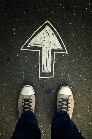 スニーカー: 男性に描かれた方向矢印の付いたアスファルトの道路上のスニーカー