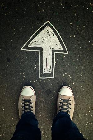Man sneakers op de asfaltweg met getrokken richtingspijl