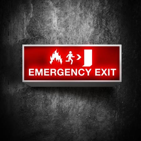 iluminado: Emergencia por incendio señal de salida en la pared del grunge obsoletos Foto de archivo