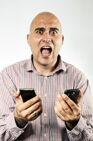 Stressed young adult businessman using two smartphone device at the same time, looking really stressed and hassled photo