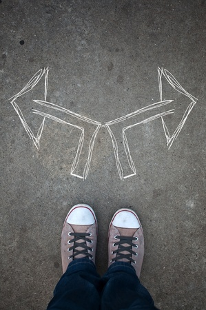 instructions: Male sneakers on the asphalt road with drawn direction arrow