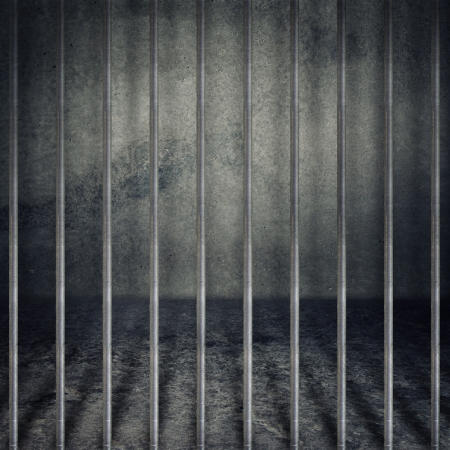 Obsolete gray grunge concrete room, prison cell with metal bars. Stock Photo
