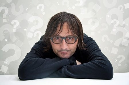 casualy: Casualy dressed man is sitting at the table and thinking, question marks around his head