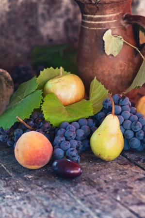 Old wooden table full of various fresh autumn fruit: apple, pear, grape, plum and peach. photo