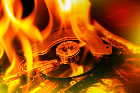 Close up image of computer hard disk on fire, burning in flasmes.