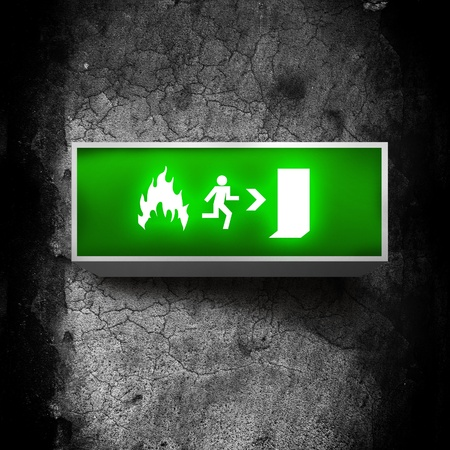 fire safety: Fire emergency exit sign on a grunge obsolete wall