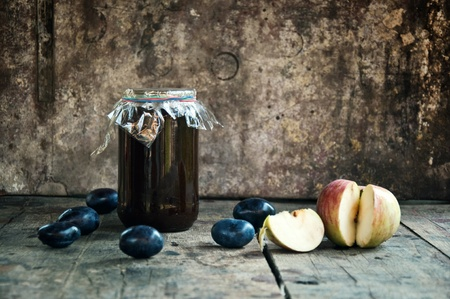 Jar of plum jam on a wooden table with some plums and an apple, organic food production photo