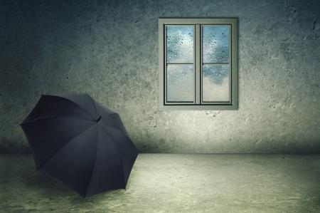 window pane: Forgotten black umbrella in a cold concrete room, rain drops on window pane. Stock Photo