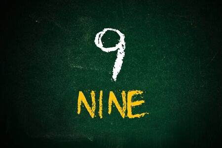 literate: Number nine, handwritten number nine with a chalk on a green chalkboard.