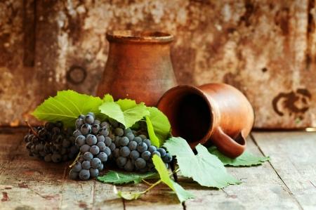 ollas de barro: Las uvas frescas sabrosas maduras en una vieja mesa de madera