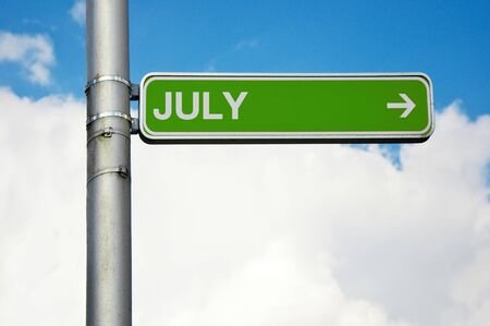 green street sign: Green street sign - July with arrow pointing to the right, cloudy sky in the background