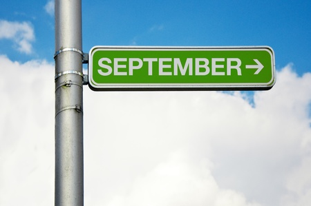 green street sign: Green street sign - September with arrow pointing to the right, cloudy sky in the background  Stock Photo