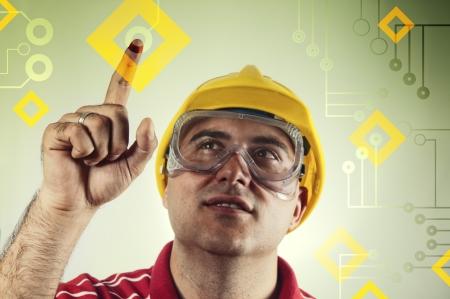 ingeniero civil: Joven trabajador de la construcci�n en camisa roja con el sombrero amarillo duro presionando una pantalla t�ctil con su dedo �ndice generado por ordenador interfaz gr�fica represnt ordenador gr�fico moderno para la industria de la construcci�n