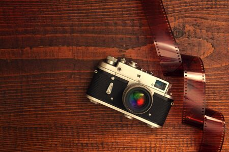 overexposed: Retro style camera on a wooden table plate with some 35 overexposed film strip