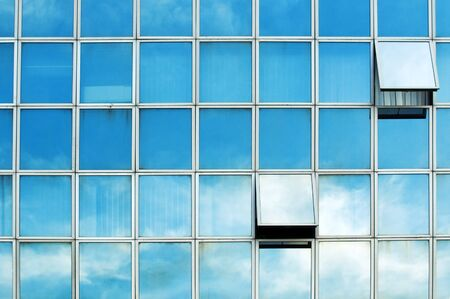 Windows on the office buildings with clouds reflecting photo