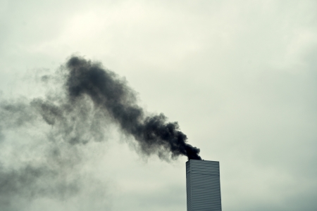 intoxication: Dark black smoke from the chimney on a cold, cloudy day.
