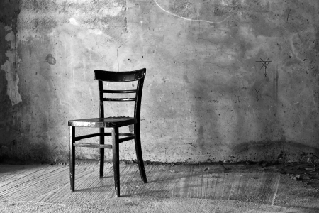 Vintage old black wooden chair in grungy interior. Loneliness, estrangement, alienation concept. photo