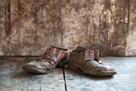 muddy clothes: Old dirty brown leather shoes on wooden floor. Stock Photo