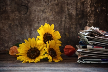 Sunflower and a stack of newspaper, autumn still life on the old wooden table  Stock Photo - 16221058