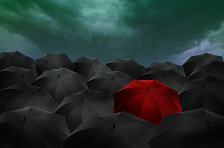 Standing out from the crowd concept, red umbrella among the blacks  photo
