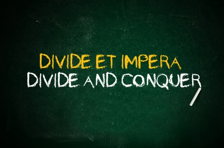divide: Divide and conquer. Latin quote handwritten with chalk on a green school board. Stock Photo