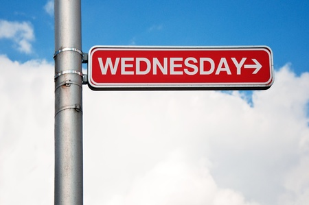 wednesday: red street sign - wednesday with arrow pointing to the right, cloudy sky in the background.
