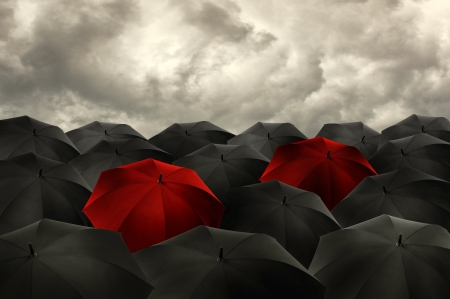 alone in crowd: Standing out from the crowd concept, red umbrella among the blacks. Stock Photo