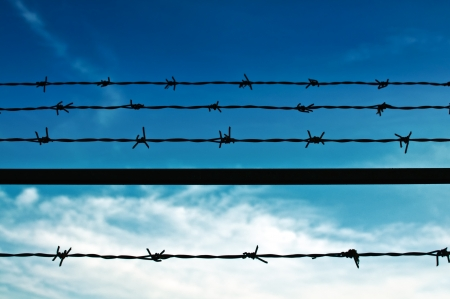 criminal defense: Barbed wire fence against the blue sky Stock Photo