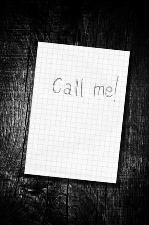 wall paper texture: Call me, reminder paper note over a wooden background, black and white image.