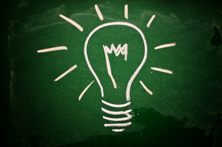 creative solutions: A lightbulb drawn on a green chalkboard symbolizing ideas, inspiration and creativity