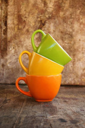Colorful coffee mugs over an obsolete grunge wooden background photo