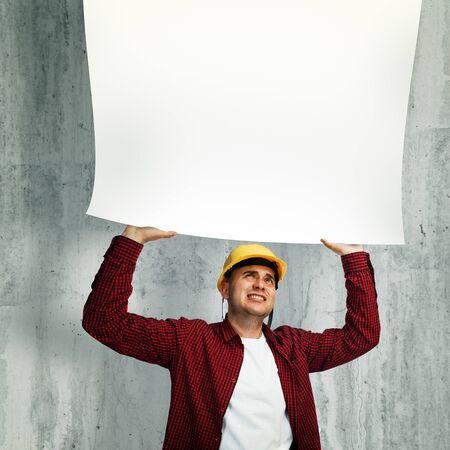 industry architecture: Construction worker with yellow hard hat in red shirt holding a whiteboard above his head.