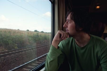 persona viajando: Adulto masculino viajar en tren, mirando por la ventana Foto de archivo