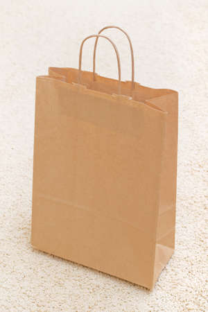 Empty shopping paper bag on a bright carpet photo
