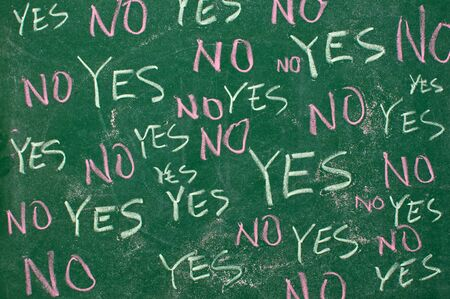 Yes and no concept; words written with chalk on the green board photo