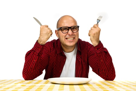 young knife: Young adult bold man sitting at the dinner table with fork and knife raised.