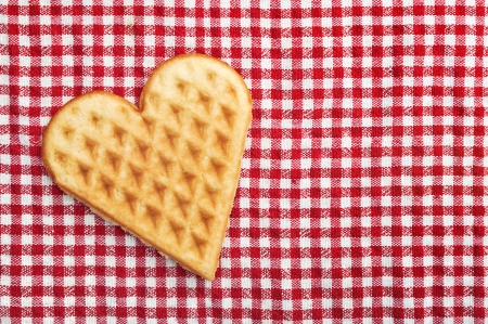 Heart shaped galette cookie on red and white checkered table cloth. photo