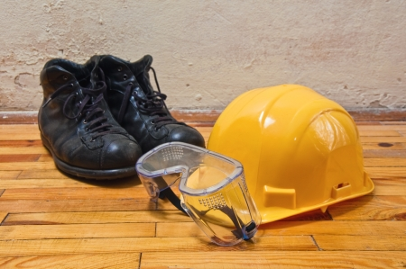 safety boots: Yellow hard hat, old leather boots and protective goggles, protective equipment in construction industry.