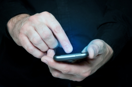 message: Man in black shirt is typing a text message on his smartphone, close up image, focus on hands and the phone device.