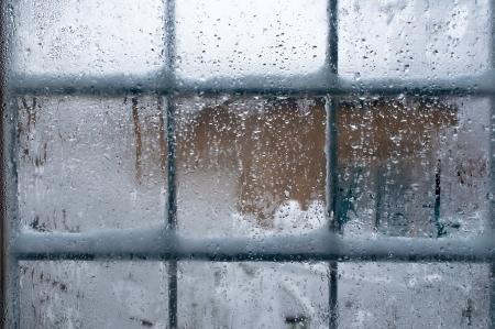 Inverno finestra, gocce d'acqua e fiocchi di neve su vetro di una finestra.