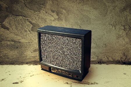 Old TV in grunge cement room, no signal photo